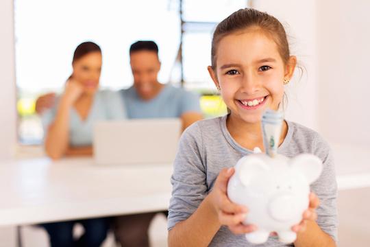 little girl holding piggybank
